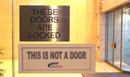 Juxtaposition of THESE DOORS ARE LOCKED and THIS IS NOT A DOOR signs